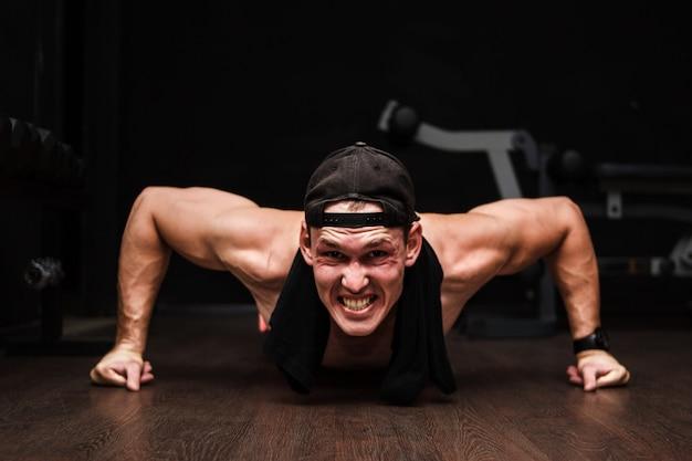 ボディービルのトレーニングの一部としてプッシュアップを行う若い大人の運動選手