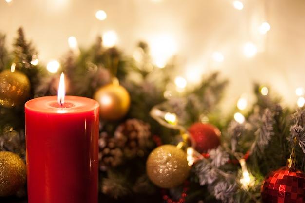 クリスマスツリーと輝く花輪の枝のクリスマスキャンドル