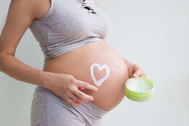 妊娠中の女性が赤いハートと彼女の腹、新しい生命の象徴、赤ちゃんを期待して家族を拡張することの概念に手を握って