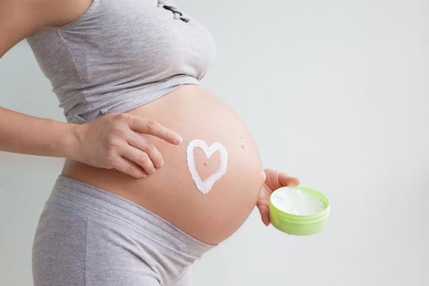 妊婦さんがお腹にストレッチマーククリームを塗っています。ストレッチマーク。線条。妊娠中の肌に潤いを与えます。ボディスキンケア。妊娠。マタニティ。