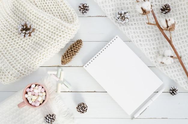 クリスマスの冬の組成。空のメモ帳、モミの木、コーン、綿。