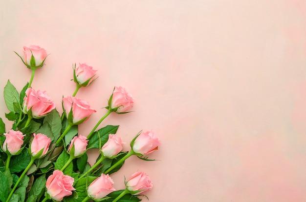 ピンクのパステルカラーの背景上の隅にフラットレイアウトブーケバラ。