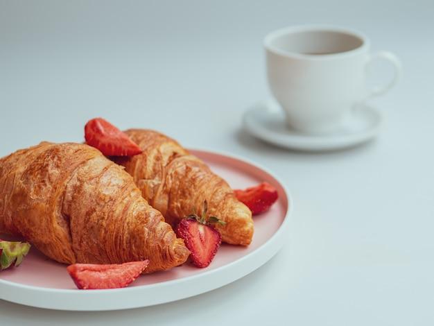クロワッサン、イチゴの新鮮な朝食、コーヒーを飲みながらの夏の朝。閉じる