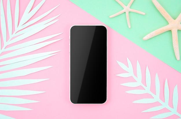 紙のヤシの葉とポップなパステル調の背景に空白の画面を持つフレームスマートフォン