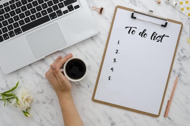 オフィスワークフラットレイ。クリップボードにリストを書く少女。コンピュータ、消耗品、コーヒー