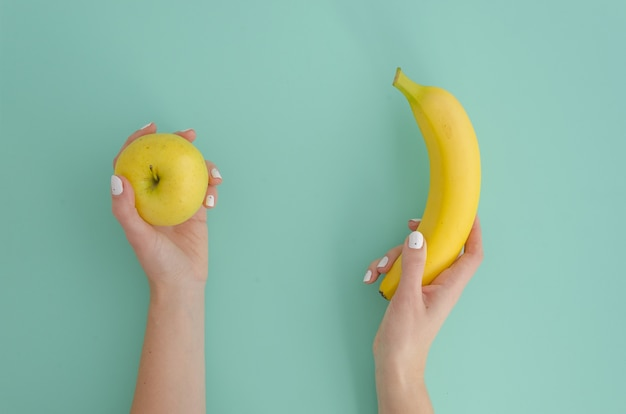 黄色の小さなリンゴと熱帯のバナナを持つ女性の手
