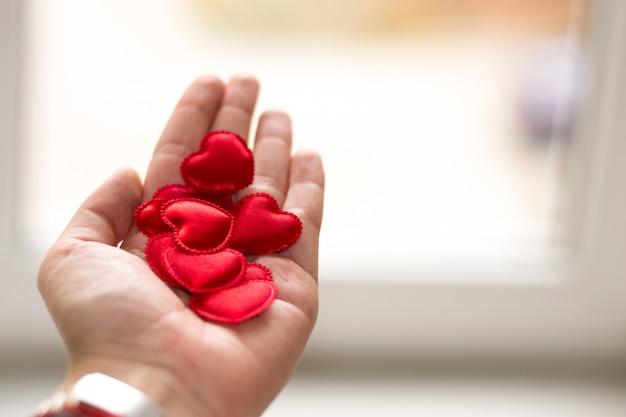 Копировать пространство день святого валентина. маленькие красные сердца в руке на белом. человек отдает свое сердце женщине