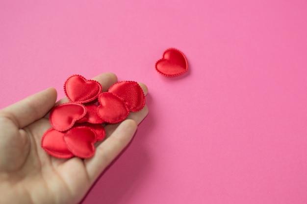 Мужчина дарит сердце женщине. копировать пространство день святого валентина. маленькие красные сердечки в руке на розовом ба
