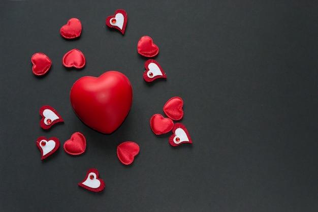 Большое красное сердце среди маленьких на черном фоне. копировать пространство символы дня святого валентина