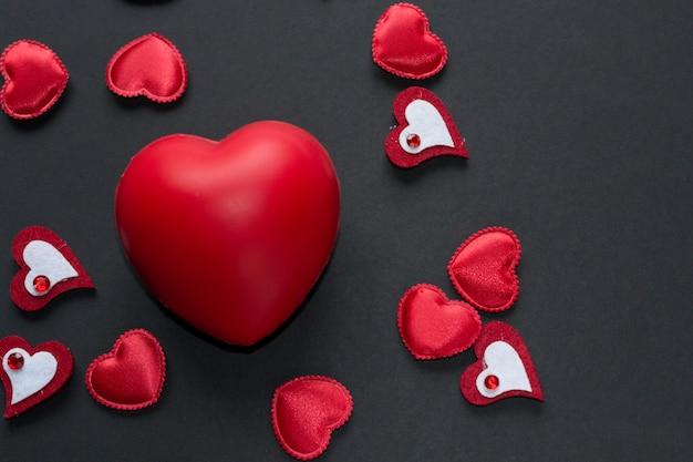 Закройте красные сердца на черном фоне. день святого валентина концепция - символы любви.