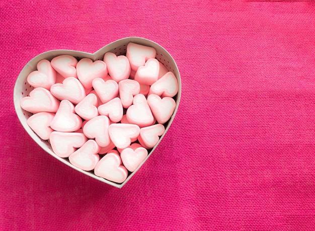 ピンクのキャンバスにハートの形のギフトボックスにピンクのマシュマロ