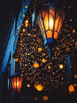 魔法のオールドストリートランタンが夜通りに輝いています。周りにたくさんの明るいライトがあります。家の壁にヴィンテージオールドストリートクラシックアイアンランタン。クリスマスやハロウィーンの魔法の妖精提灯。