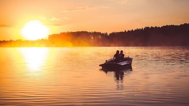愛のカップルは日没時に湖で手漕ぎボートに乗る。黄金の時間でロマンチックな夕日。