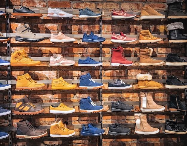 店の窓の中の靴。さまざまな男性用および女性用の靴のスニーカー、ブーツ、市場でのショーケースにのせもの。