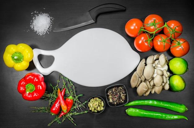 Белая разделочная доска среди овощей, нож и соль.