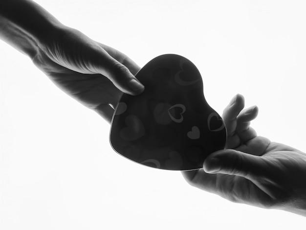Силуэт руки с подарочной коробке. присутствует в мужских и женских руках в форме сердца белого цвета.