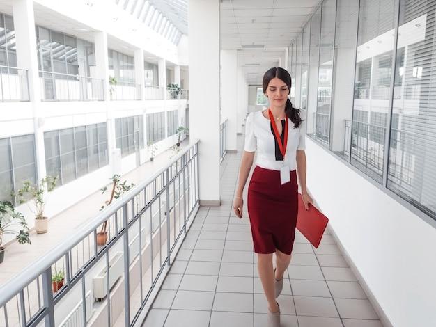 Деловая женщина, прогуливаясь по офисному коридору.