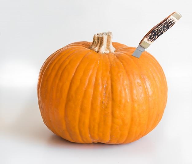 Маленькая оранжевая тыква и нож застряли в изолированных на белом