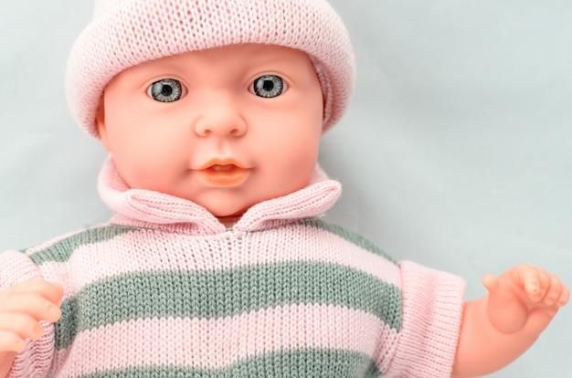 ニットドレスの女の子のためのかわいい赤ちゃん人形をクローズアップ