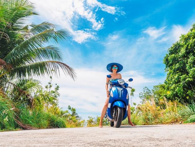 Смешная девчонка на мотоцикле на фоне голубого неба и зеленых тропиков