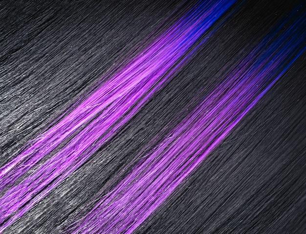 着色された紫色の薄紫色の青いストランドと美しい滑らかなブルネットの髪。
