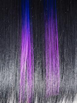 光沢のあるストレートの黒い髪の背景。着色された紫色の薄紫色の青いストランドと美しい滑らかなブルネットの髪。美容トレンド