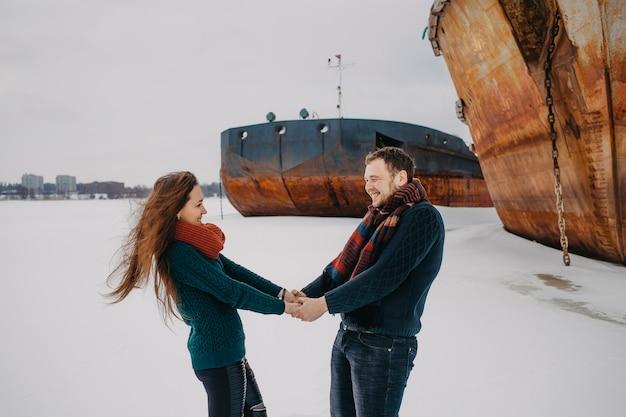 冬には、船の横にある凍った川の上を男女が歩きます。