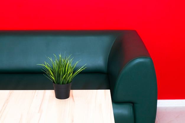 緑のソファと赤い壁のオフィスインテリア。