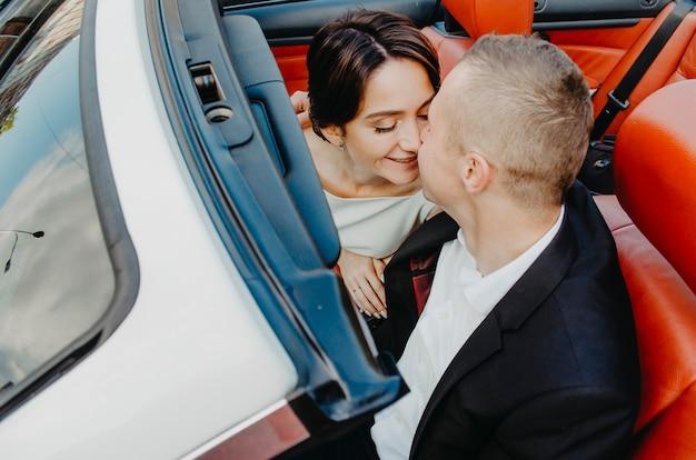 コンバーチブルトップビューで愛情のあるカップルのキス。