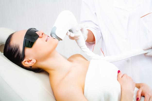 顔にレーザーを当てて脱毛を行う手順に関する患者のクローズアップ写真。