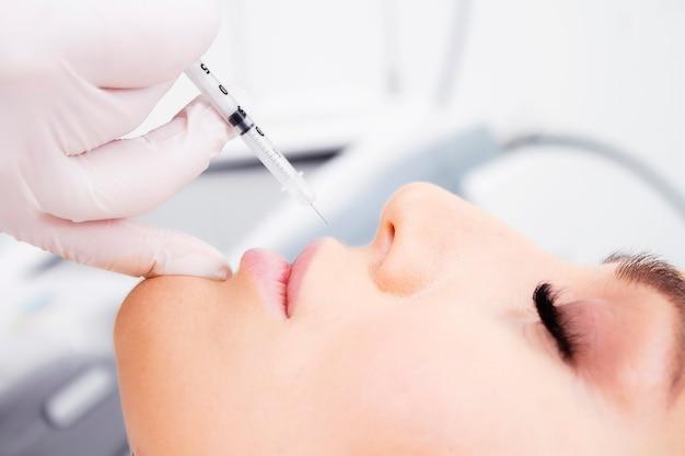 Крупный план процедуры увеличения губ.