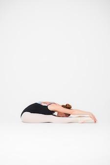 柔軟なバレリーナは、白い背景の教室でリハーサルのために伸びています。