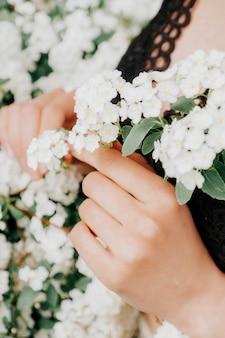 女性の手に白い花が咲く枝