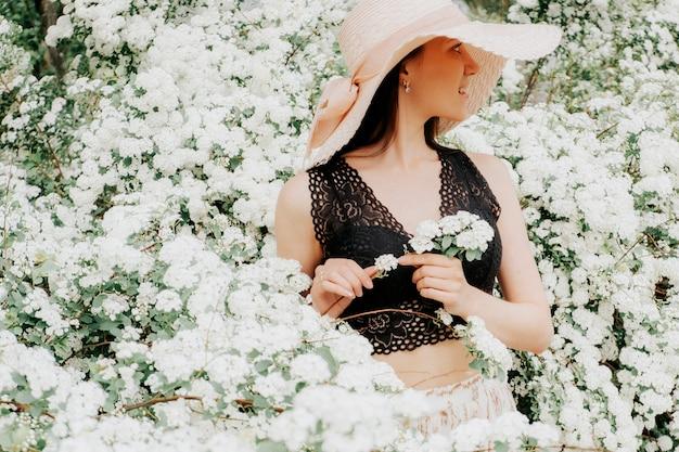 花の咲く庭で帽子の少女