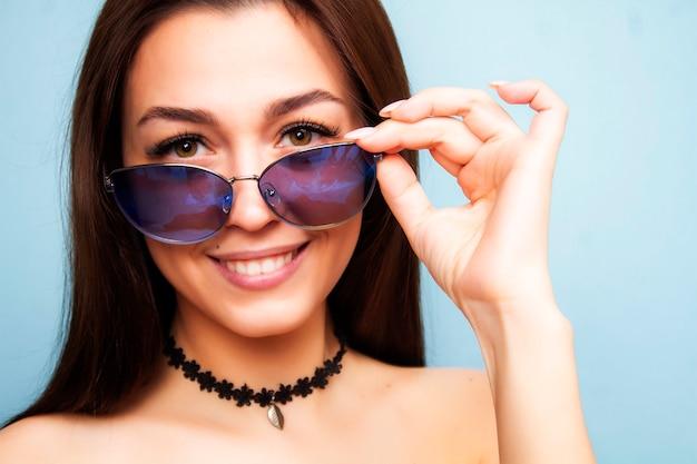 水色の壁にサングラスの女の子