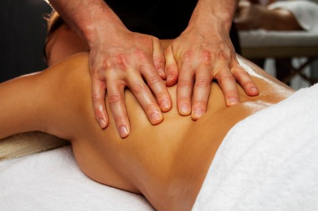 Массажное масло. тайский массаж с маслом крупным планом. массаж спины. спа-процедуры.