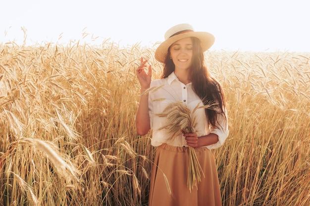 麦畑の女の子。日没時のライ麦の写真。耳を持つ女性。