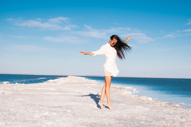 海沿いのビーチドレスで美しい少女。塩湖の女性。死海で休憩。