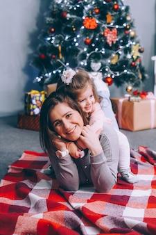 幸せな母と娘は、笑って飾られたクリスマスツリーの下に横たわっています。