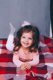 赤い格子縞にある美しい巻き毛の少女