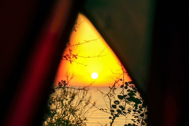 Прекрасный вид на восход солнца на море из палатки через ветки