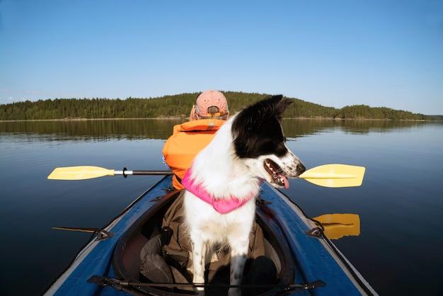 カヤックボートに浮かんでいるライフジャケットの所有者と犬