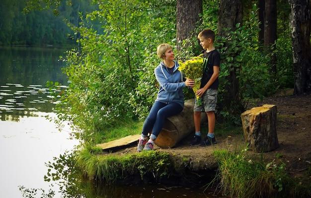 Сын дарит цветы своей матери на природе на озере.