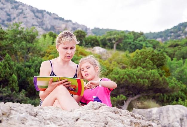 Дочь слушает, как ее мать читает ей книгу летом на природе.