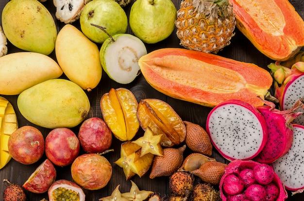 Ассорти из тайских тропических фруктов на темном деревянном деревенском фоне.