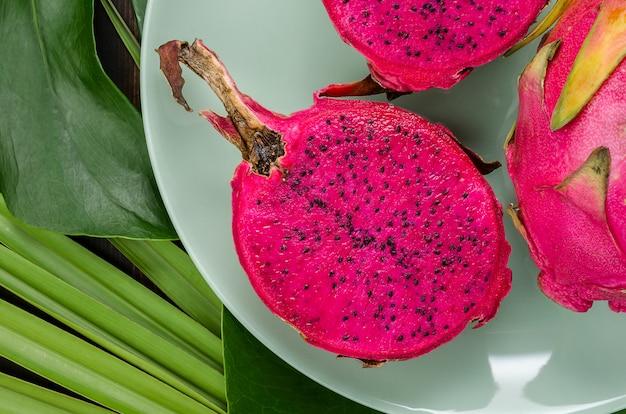Плод дракона на зеленой тарелке. темный фон с пальмовых листьев.