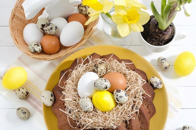 Кулич с крашеными яйцами в гнезде, нарциссами и гиацинтом в чашке на белом деревенском деревянном фоне