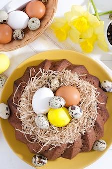 素朴な木製の白地にカップの水仙の巣の染め卵イースターケーキ