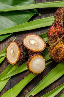 Рамбутан на фоне зеленых листьев пальмы.