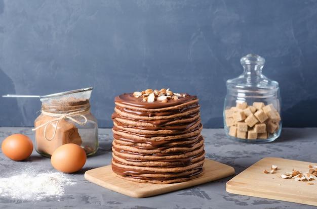 Блинный торт. стек шоколадные блины с шоколадным кремом и миндалем на вершине.